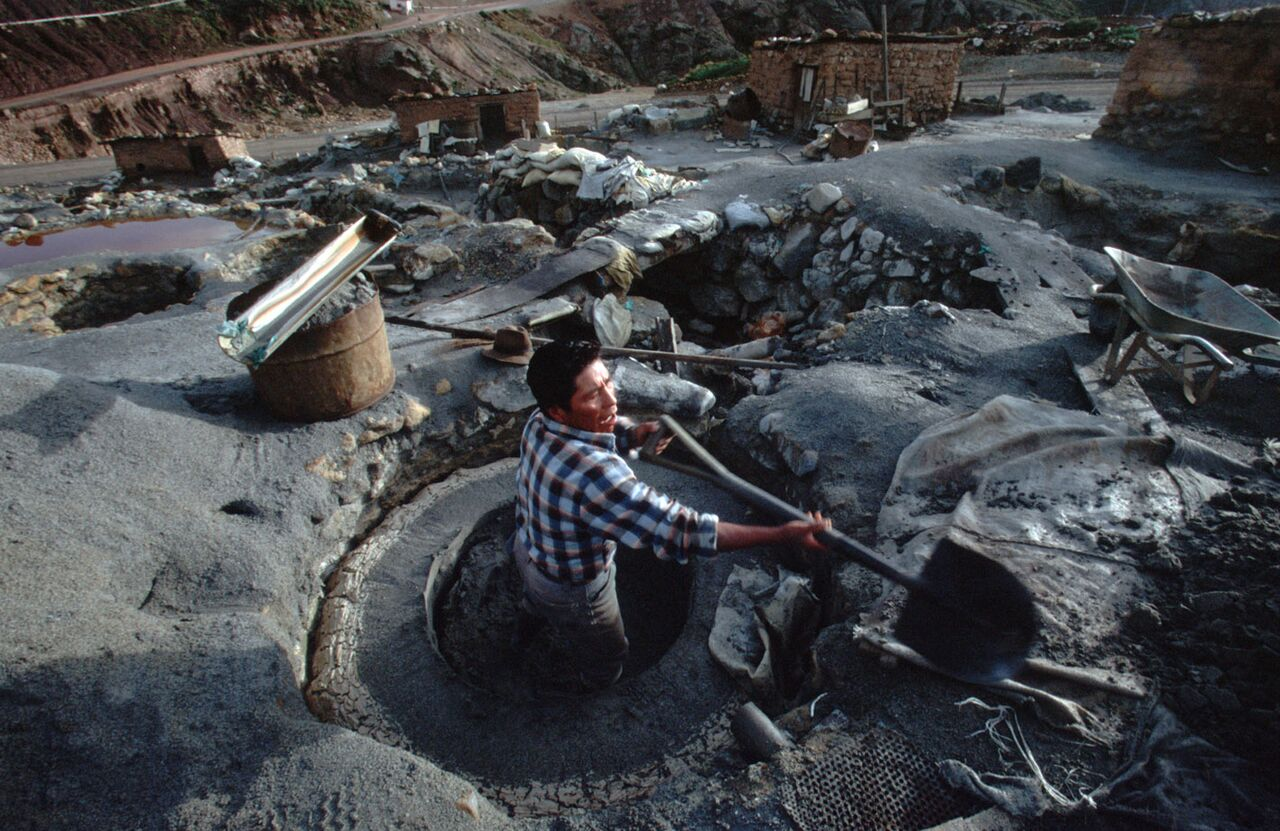 The awful life. This Bolivian Quechua man shovels the mine tailing dregs. He does this every day, all day in a chemical-laden quarry. The hut where his family lives is just beyond him. He does it all hoping to score about 50 cents a day. The fumes alone nearly choked me. James Yates photo.